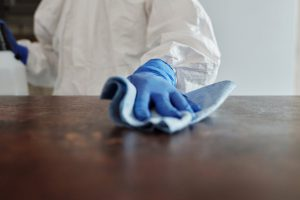 A person in a PPE suit and gloves cleans a surface with a towel and sanitizing spray.